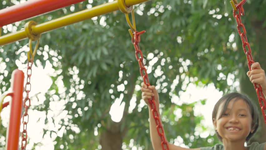 Slow motion footage of happy little girl playing on the swing in summer park | Shutterstock HD Video #1013070857