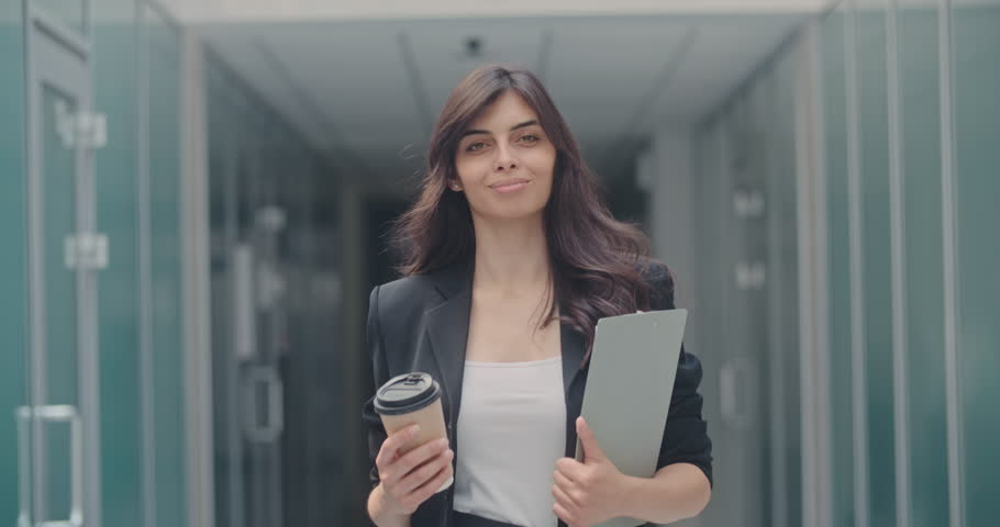 Portrait of young successful businesswoman walking in office hall with pad and cup of coffee in her hands, looking at camera and smiling 4k | Shutterstock HD Video #1013074283