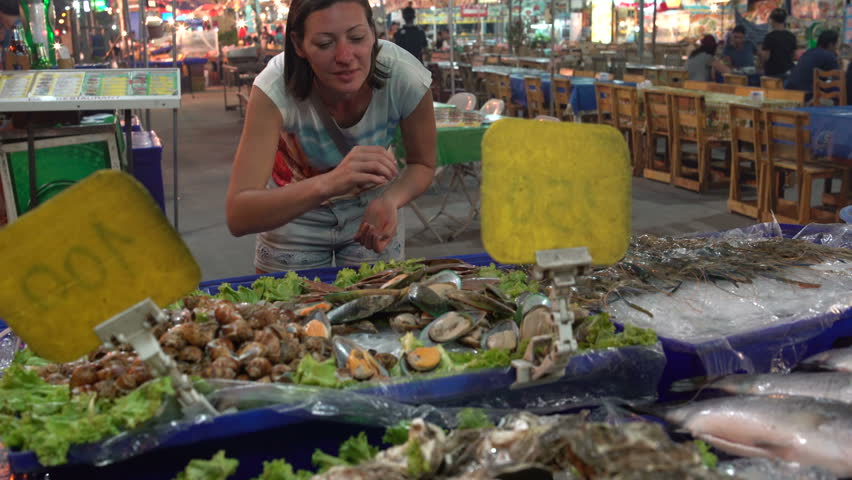 The woman takes shells with shellfish from the counter with seafood. Street food