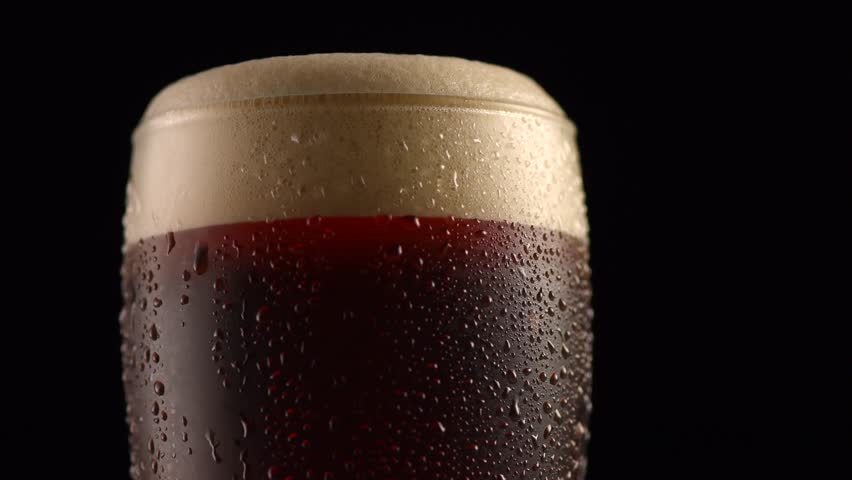 Dark Beer closeup. Pint of cold Craft beer isolated on matte black background, rotation 360 degrees. Glass of beer with water drops. 4K UHD video 3840x2160 #1013081378