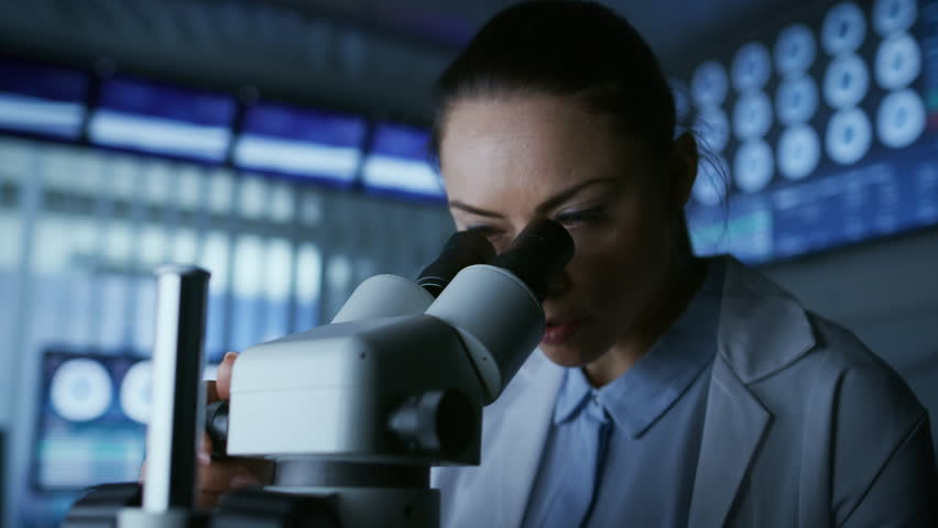 Medical Research Scientist Looking under the Microscope in the Laboratory. Microbiologist, Chemist, Neurologist Solving Puzzles of the Mind and Mind and Brain