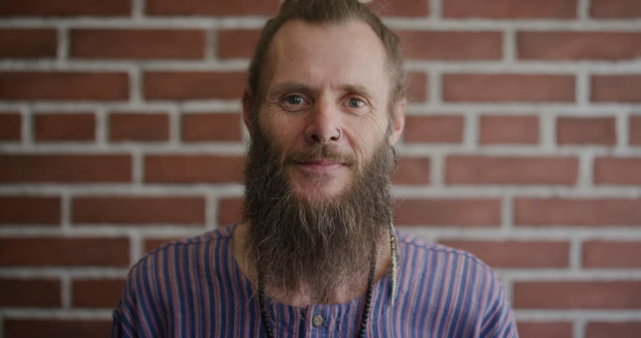 Portrait of mature bearded hippie man smiling, enjoying relaxed carefree lifestyle #1013085992
