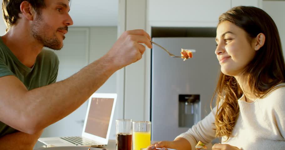 Man feeding food to his woman at home 4k