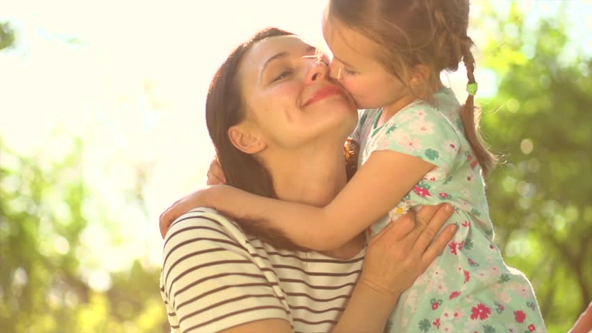 Beautiful Mother And her little daughter outdoors. Nature. Beauty Mum and her Child playing in Park together. Kissing and hugging happy family. Happy Mother's Day Joy. Mom and Baby. Slow motion 4K