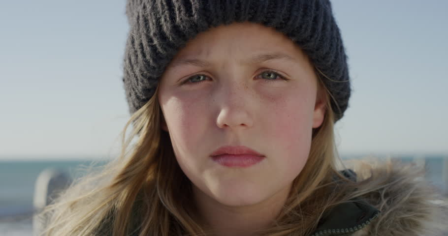 close up portrait cute little caucasian girl looking serious wearing warm clothes beanie on seaside beach contemplative child real people series #1013096753