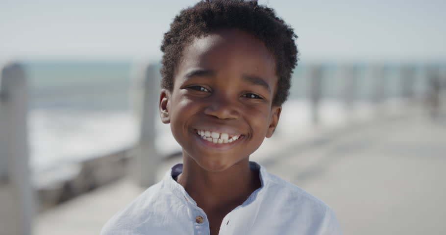 Close up portrait happy african american boy smiling cheerful enjoying warm summer vacation on seaside beach waterfront slow motion