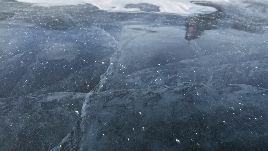 Man is pouring snow on the ice. Slow motion. Particles of snow beautifully scatter on the ice. The guy in the mittens cleans the ice. Ice with magical cracks.   Shutterstock HD Video #1013123489