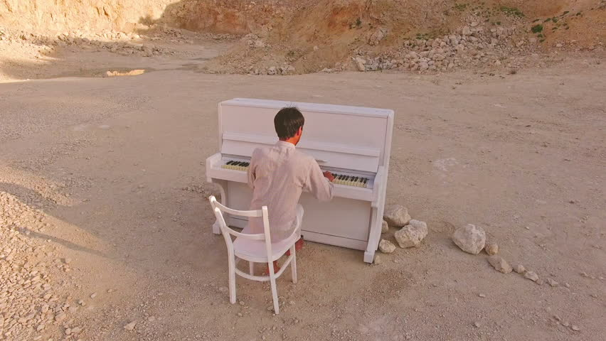 Young man plays the piano on a background of yellow mountains and stones | Shutterstock HD Video #1013131577