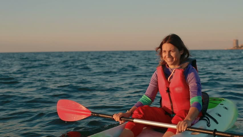 Attractive young woman in the morning on the open sea kayaking rowing oars. in slow motion   Shutterstock HD Video #1013144981