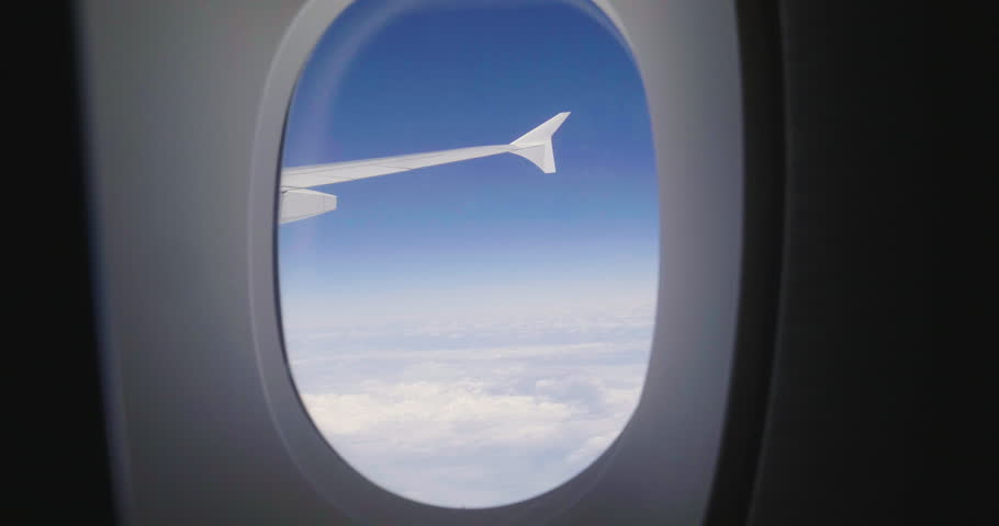Close-up of an airplane seat on which a person relaxes while flying, to go on vacation, and the clouds of the sky can be seen from the window. Concept of: travel, vacation and transport and comfort. #1013157986