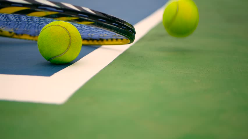 Close up of tennis equipment on the court. Sport, recreation concept. Yellow racket with a tennis ball in motion on a clay green blue court next to the white line with copy space and soft focus. #1013158994