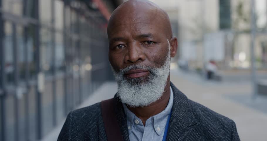 portrait successful senior african american businessman in city enjoying professional urban lifestyle mature black man commuter slow motion real people series