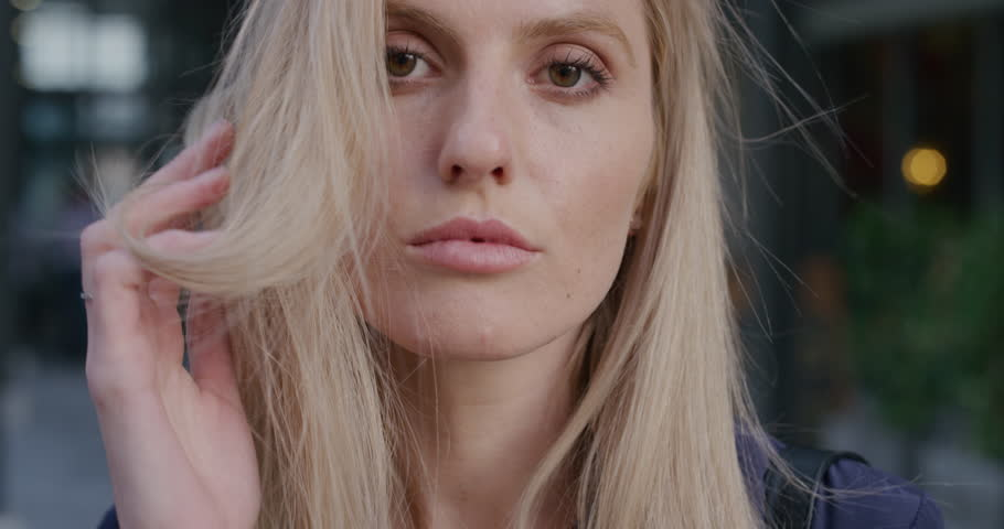 close up portrait young attractive blonde woman running hand through hair slowly looking sensual seductive female in city slow motion #1013162186