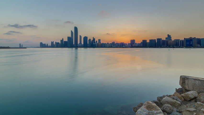 Abu Dhabi city skyline on sunrise time with water reflection timelapse from the Breakwater near cultural village. Few clouds on morning sky