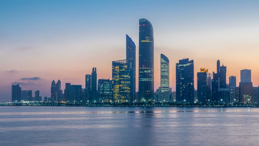 Abu Dhabi city skyline with skyscrapers before sunrise with water reflection night to day transition timelapse from the Breakwater near cultural village. Few clouds on morning sky