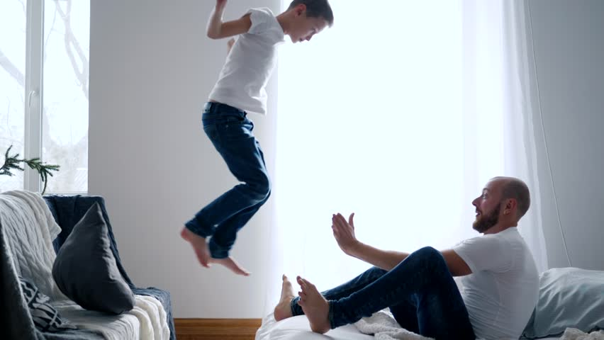 happy family idyll, son jumps in hands father and they fall on a bed in slow motion #1013180975