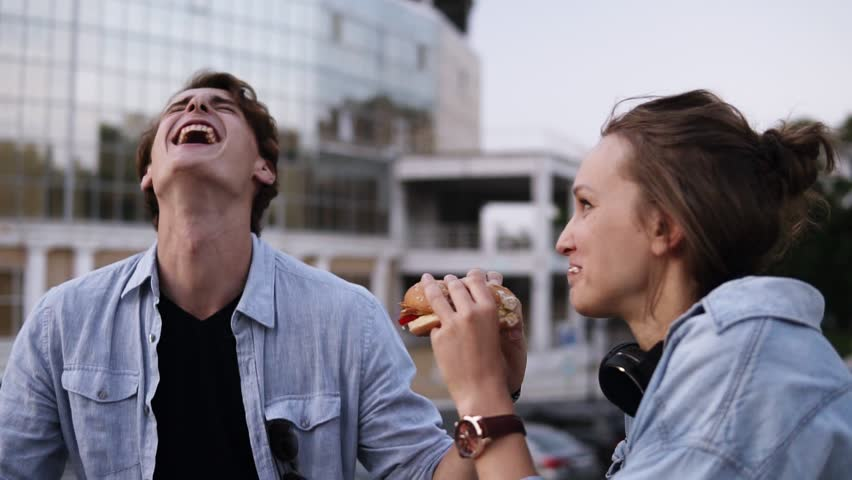 Happy, young couple are hanging out in the park. Lauging and smiling. Girl is eating burger. The young guy gently wipes the sauce off his girl's lips and licks a finger. Close up | Shutterstock HD Video #1013181446