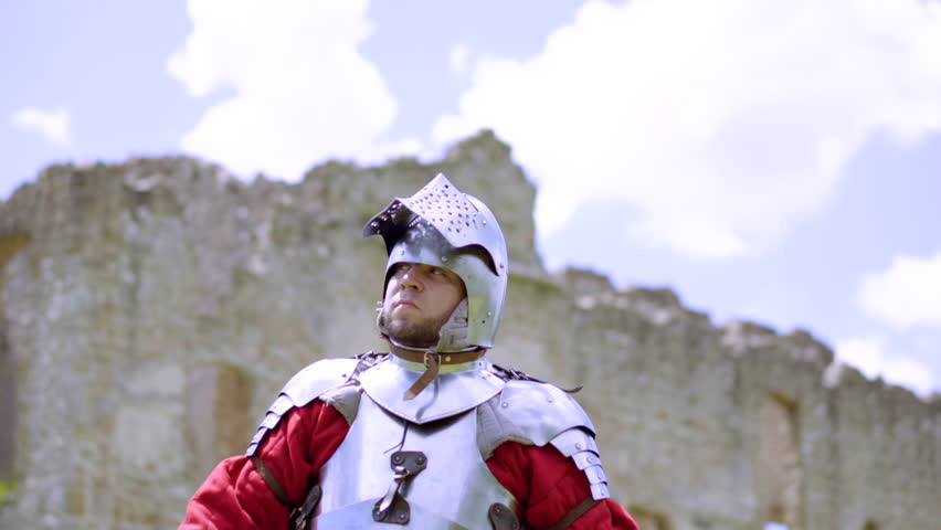 Medium shot of knight drawing his swordA knight with a sword protects the castle and walks around the castle | Shutterstock HD Video #1013186420