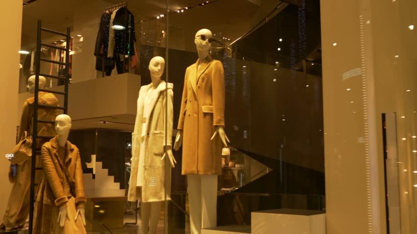 Elegant female mannequins near stairs in a fashion shop showcase
