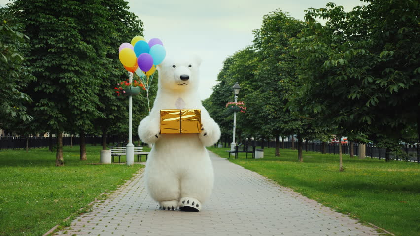 A large polar bear walks down the street, carries balloons and a box with a gift. Birthday gifts and a cool party concept