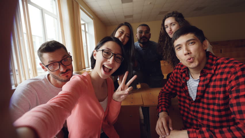 Point of view shot of attractive young men and women taking selfie in lecture hall, posing with textbook and showing hand gestures and expressive faces. #1013200445