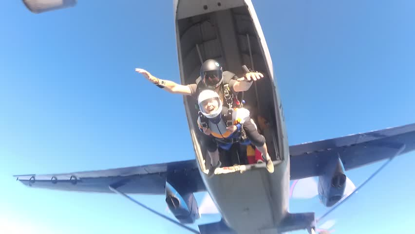 Skydiving. Tandem is jumping out of a plane and two friends are flying to the one. | Shutterstock HD Video #1013204147