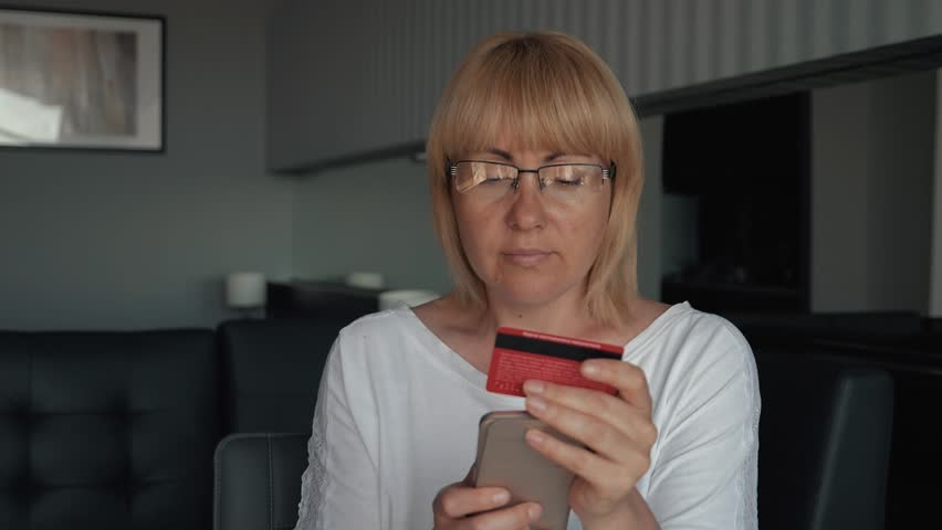 The girl pays for the purchase on the Internet. A female consumer using laptop computers to pay for a purchase in an online store. E-commerce website payments concept. Pay for online purchases on the  Royalty-Free Stock Footage #1013206016