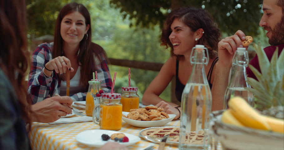 group of friends doing breakfast outdoors in a traditional countryside. shot in slow motion #1013208314