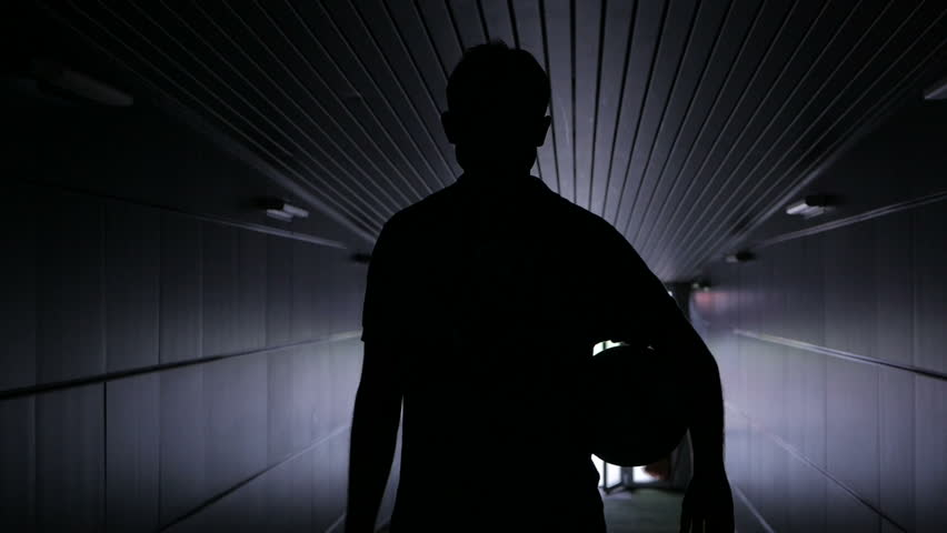 Two football players are walking along a dark tunnel to the football field. View from the back