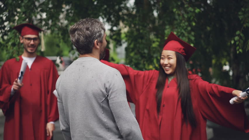 Happy daughter graduating student is embracing her loving father bearded man and laughing, girl is holding diploma and wearing mortar-board and gown.