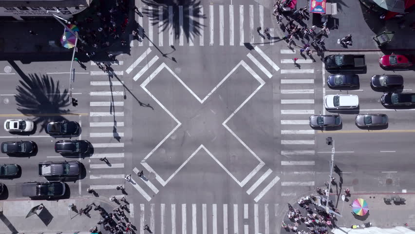 Busy crosswalk intersection. Crowds of both tourists and other city people cross diagonally through a bustling part of town. Shot in Hollywood, Los Angeles