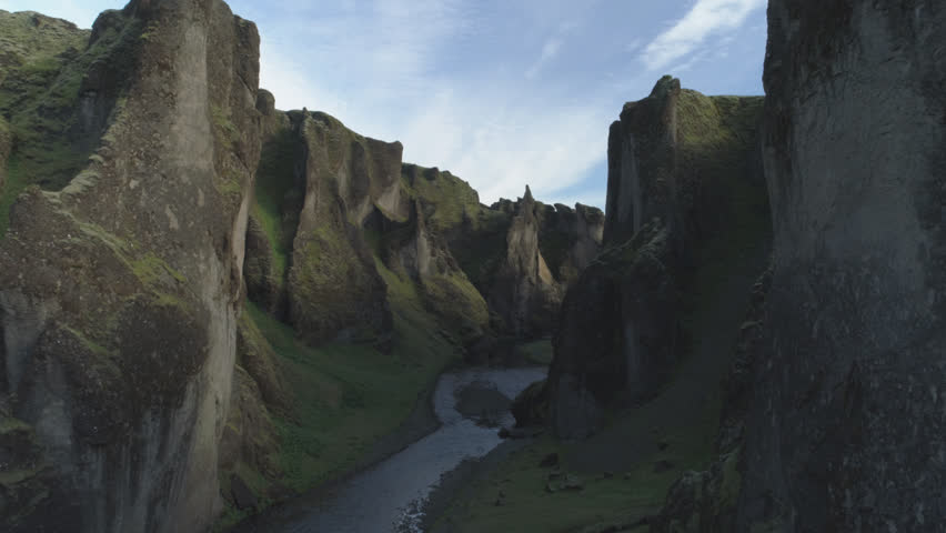 Fjadragljufur river canyon, steep rock walls, slow forward aerial shot, Iceland.