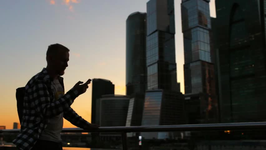 Silhouette of a man with a phone at sunset near skyscrapers | Shutterstock HD Video #1013264078