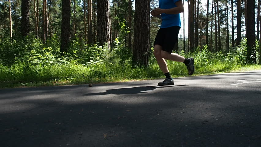 Male athlete jogging in the morning. Runner man running on park path exercising on beautiful summer day. Sports and recreation activity. Young active man training doing recreational jogging workout.  | Shutterstock HD Video #1013266610