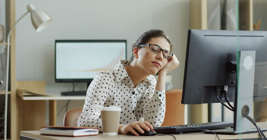 Young tired woman in glasses sitting at the laptop computer while working in the office, then almost falling asleep and waking up. Indoor.