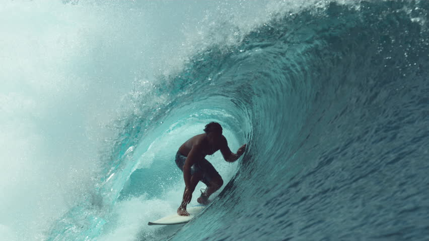 SLOW MOTION, CLOSE UP: Extreme sportsman having fun riding a beautiful barrel ocean wave. Breathtaking shot of active man on holiday surfing a perfect crystal clear hollow wave in Teahupoo, Tahiti.