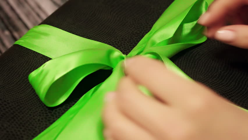 Woman hands untie green ribbon on black gift box. Lockdown shot of tender female hands unpacking present on wooden table. Personal perspective of lady unpacking box. 4k UHD.