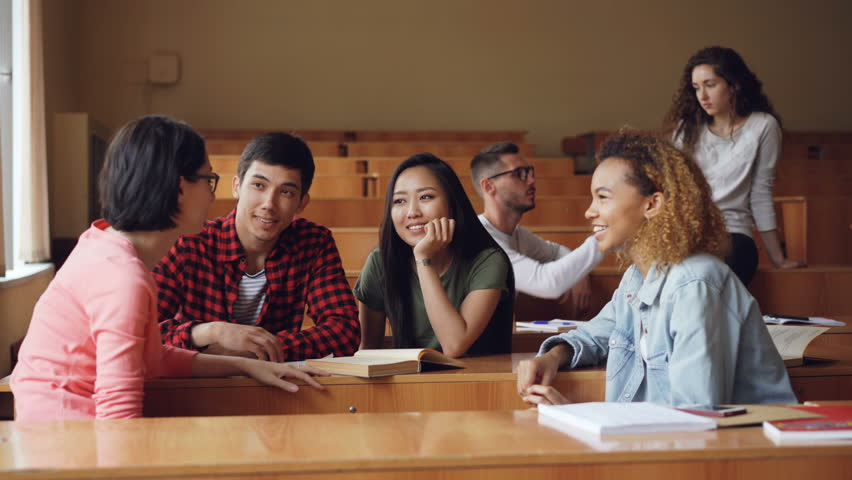 Careless girls and boys are talking and laughing sitting at desks in lecture hall, students are relaxing during break. Conversation, modern education and youth concept.