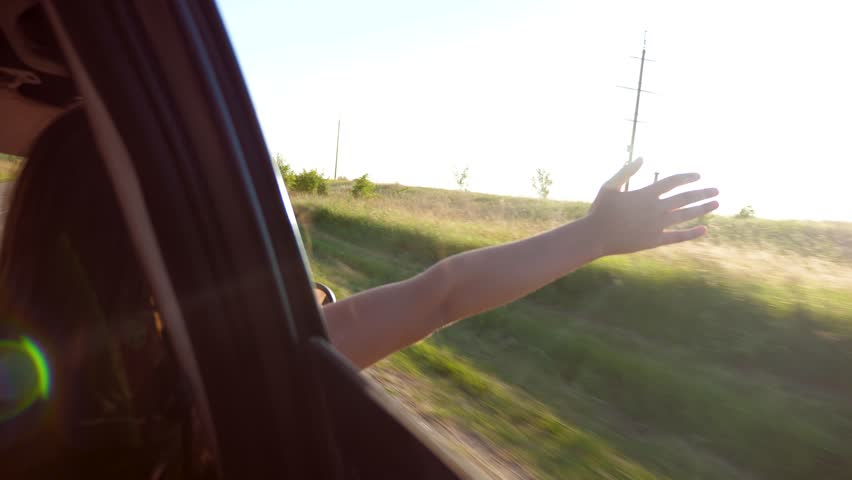 Girl with long hair is sitting in front seat of car, stretching her arm out window and catching glare of setting sun.