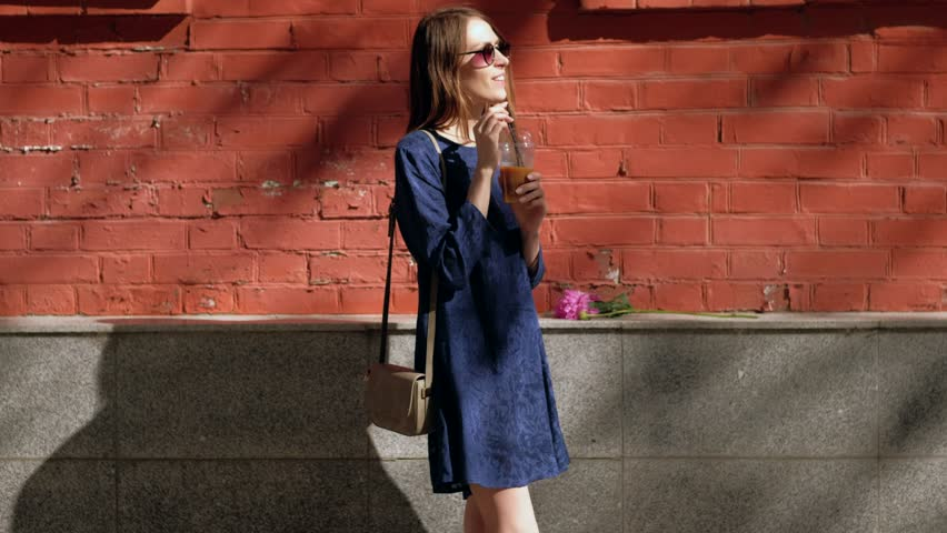 Women in a blue dress drinking a coffee cocktail on the street at the red wall. | Shutterstock HD Video #1013308388
