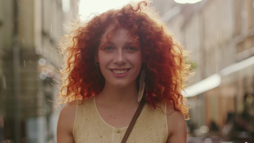 Young smiling attractive woman with red curly hair walking in the rain on the street look at camera spinning happy cute fashion water silhouette summer face female lonely stop close up   Shutterstock HD Video #1013312204
