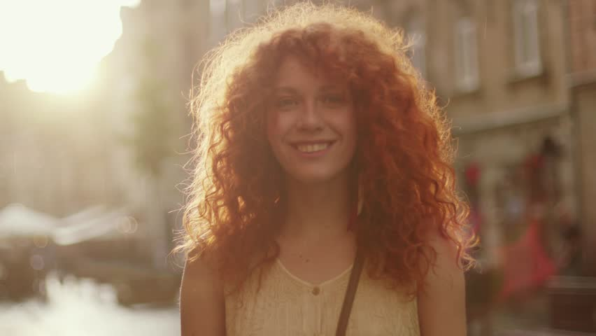 Sunshine young smiling woman with red curly hair look at camera smile walking in the city streets portrait happy slow motion summer face sunset beautiful lady outdoor closeup cute #1013313149