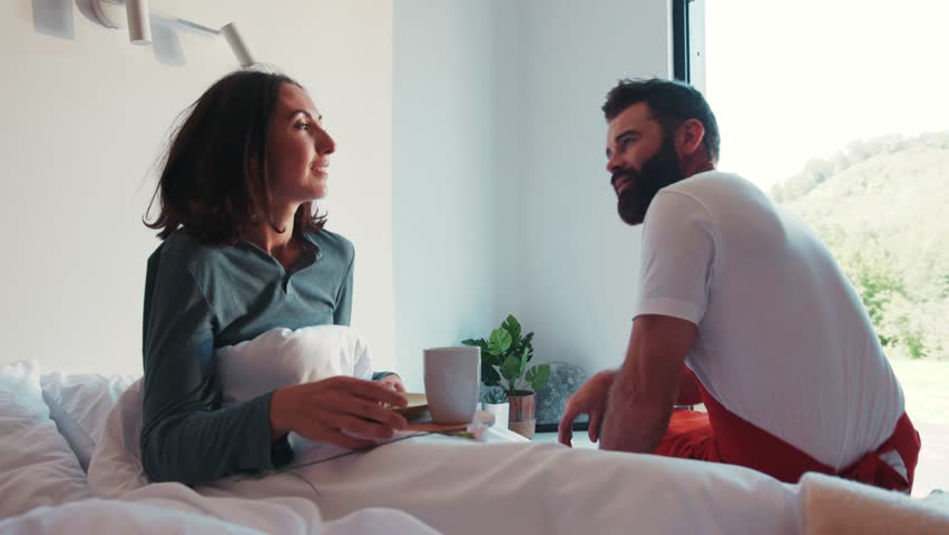 Attractive strong romantic bearded man in a red apron brings his wife a flower and breakfast in bed, talking to each other. Couple goals, true love, love story. Happy together, man's power. #1013313437