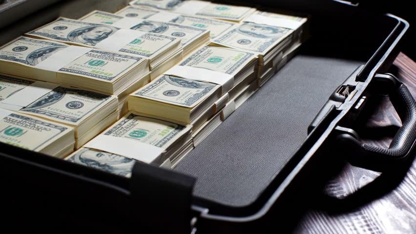 Men packing 100 US dollar bills in to briefcase