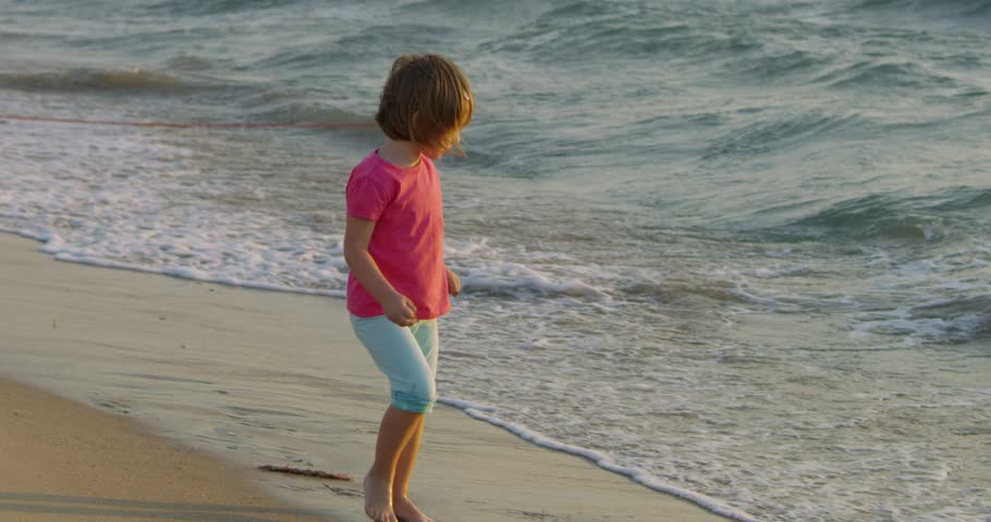 Happy family concept woman mother and girl having beautiful time and fun while walking on beautiful golden beach with waves in slow motion | Shutterstock HD Video #1013335850