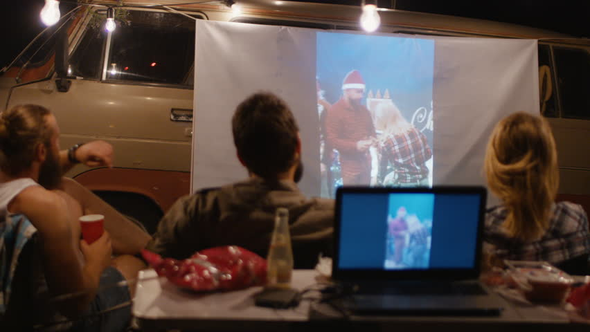 Back view of people gathering in campsite and watching home video on screen on van and with laptop behind in night | Shutterstock HD Video #1013353478