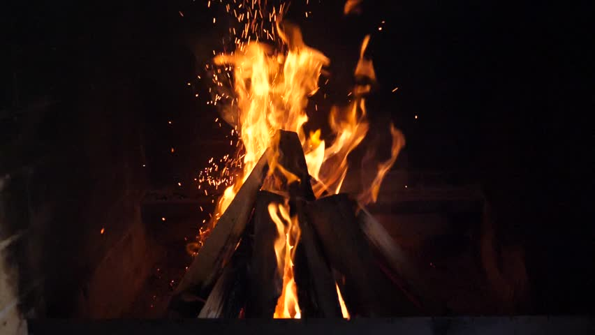 Slow motion fire. Fireplace burning. Warm cozy burning fire in a brick fireplace close up. Cozy background.