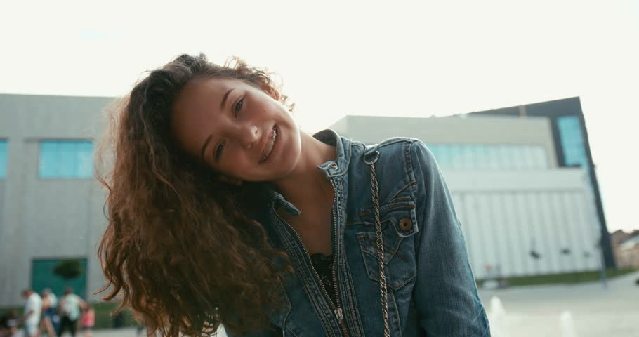 Emotional portrait of the lovely smiling girl with braces on her teeth actively shaking her dark curly hair outdoor.   Shutterstock HD Video #1013361605