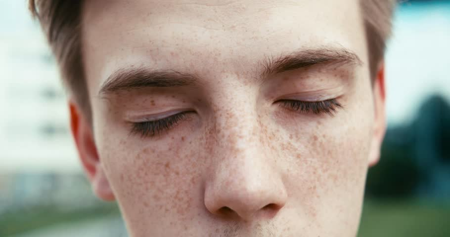 Close-up view of the guy with freckles opening his green eyes and looking at camera. 4k footage.