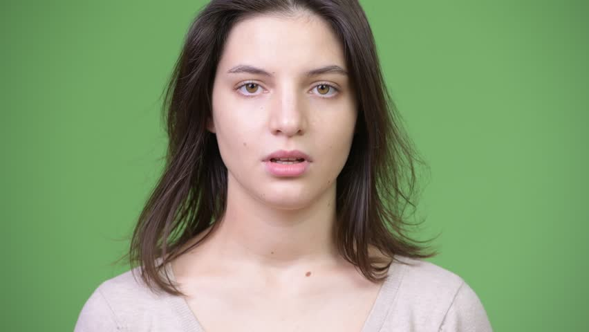 Young beautiful woman looking bored against green background | Shutterstock HD Video #1013377136